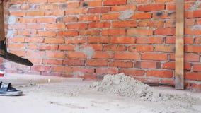 Areia de escavação da pá Conceito da constru??o Pá com areia Areia de escavação perto da parede de tijolo vermelho com pá filme