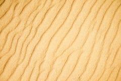 Areia de uma praia com testes padrões de onda Imagens de Stock Royalty Free