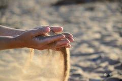A areia derrama fora das mãos fotografia de stock
