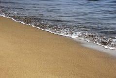 Areia do ouro e espuma do mar foto de stock