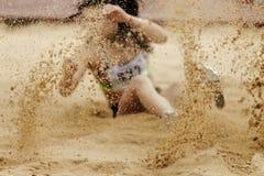 areia do pulverizador que aterra o atleta fêmea Fotografia de Stock