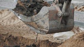 Areia do solo da cubeta da máquina escavadora e furo de escavação da sujeira no terreno de construção Slowmotion filme