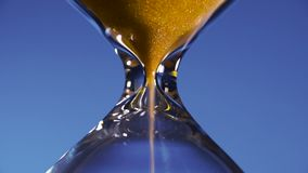 A areia dourada da ampulheta em uma garrafa transparente é derramada em um fundo azul, interrompendo o transience do tempo vídeos de arquivo