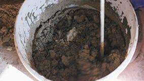 Areia e água de mistura do cimento do misturador longo da broca que criam a colagem do almofariz Movimento lento Conceito da cons filme