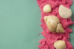 Areia e escudos cor-de-rosa sobre o fundo verde de turquesa Conceito do feriado Areia cinética fotos de stock royalty free