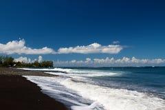 Areia e oceano pretos Fotografia de Stock Royalty Free