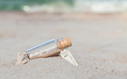 Areia e shell do mar na garrafa posta sobre a praia fotos de stock royalty free