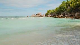 A areia fina da praia do mundo da fantasia é lavada pelas ondas espumosas do vídeo de Seychelles 4k do Oceano Índico dos azuis ce filme