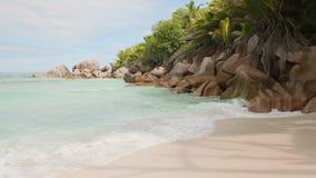 A areia fina da praia do mundo da fantasia é lavada pelas ondas espumosas do vídeo de Seychelles 4k do Oceano Índico dos azuis ce vídeos de arquivo
