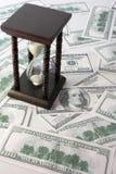 Areia-glasse e muito cem dólares Foto de Stock