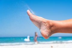 A areia goteja do pé de uma mulher fotografia de stock royalty free