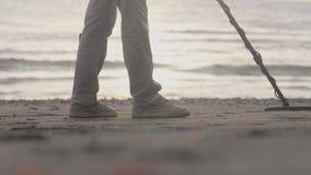 Areia irreconhecível da exploração do homem com o detector de metais eletrônico na praia que encontra artigos de valor filme