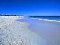 A areia molhada reflete o céu azul em uma praia australiana fotos de stock royalty free