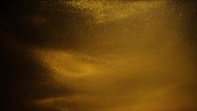 Areia ou poeira dourada que criam formações abstratas da nuvem Fundos da arte filme