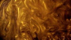 Areia ou poeira dourada que criam forma??es abstratas da nuvem Fundos da arte video estoque