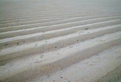 A areia pisa à esquerda pela maré Imagens de Stock Royalty Free