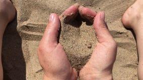 Areia que corre através das mãos colocadas filme