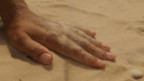 Areia seca do mar em uma mão do ` s da mulher filme
