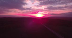 Areial view of a long straight road and a colorful sky at sunset. 4K. Areial view of a long straight road and a colorful sky at sunset stock footage