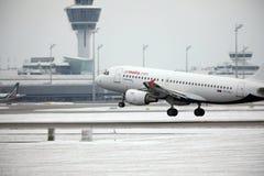 Areje a aterrissagem de Malta Airbus A319-100 9H-AEJ no aeroporto de Munich, neve em pistas de decolagem Fotografia de Stock