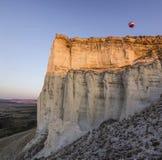 Areje baloons no nascer do sol perto da rocha branca grande Fotografia de Stock