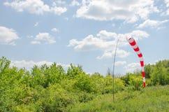 Areje o sinal de sentido do campo e um windsock da força do vento contra o céu azul com nuvens Imagem de Stock Royalty Free