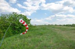 Areje o sinal de sentido do campo e um windsock da força do vento contra o céu azul com nuvens Imagens de Stock Royalty Free