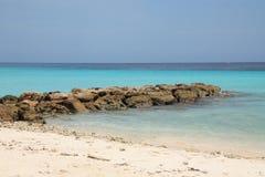 Arena blanca, mar azul y un triturador del agua Foto de archivo