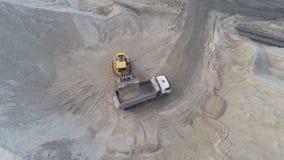 Arena cargada del cargador pesado grande de la rueda en el camión volquete en hoyo de arena Concepto pesado de la maquinaria indu almacen de metraje de vídeo