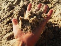 Arena de la explotación agrícola de la mano en una playa foto de archivo libre de regalías