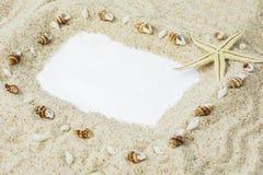 Arena de la playa con el marco y las conchas marinas fotografía de archivo