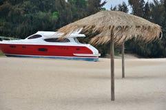 Arena de la playa y yate rojo Foto de archivo libre de regalías