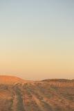 Arena de oro del desierto en la puesta del sol Pendiente en el horizonte Fotografía de archivo libre de regalías