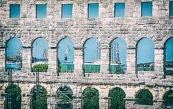 Arena dos Pula e guindastes no porto da carga, Croácia, filtro análogo imagens de stock royalty free