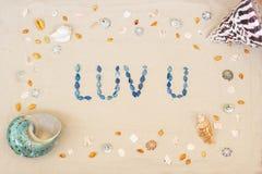 Arena en la playa en verano, el amor de la inscripción usted de las cáscaras en la arena Endecha plana Visi?n superior imagenes de archivo