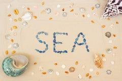 Arena en la playa en verano, el mar de la inscripción de las cáscaras en la arena Endecha plana Visi?n superior fotos de archivo
