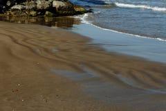 Arena en la resaca en el fondo de piedras costeras imagen de archivo
