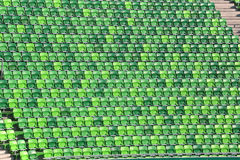 Arena with green empty tribune without people. Green plastic stadium chairs on bleachers in row Stock Photos