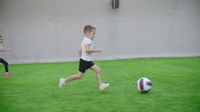 Arena interna do futebol As crianças começam jogar Um menino conduz a bola filme