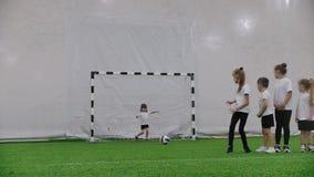 Arena interna do futebol Crianças que jogam o futebol Um rapaz pequeno tenta bater o objetivo mas a menina protege as portas vídeos de arquivo