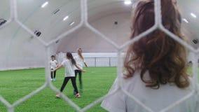Arena interna do futebol Crianças que jogam o futebol Vista atrás da grade filme