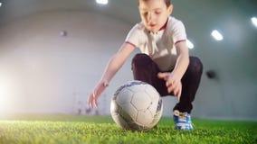 Arena interna do futebol Um rapaz pequeno que corre à bola, toma-a nas mãos e na corrida afastado vídeos de arquivo