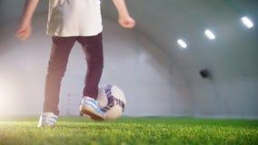 Arena interna do futebol Um rapaz pequeno que corre para a bola e para retrocedê-la vídeos de arquivo