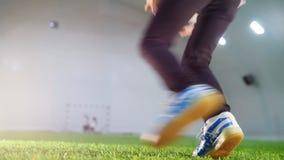 Arena interna do futebol Um rapaz pequeno que corre para a bola, toma-a nas mãos e na corrida afastado video estoque