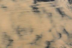 Arena mojada amarilla e inclusiones oscuras fotografía de archivo