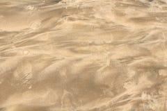 Arena mojada en la costa de mar Imagenes de archivo