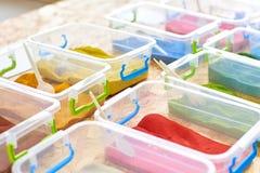 Arena multicolora para dibujar en envases de plástico imagenes de archivo