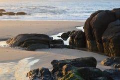 Arena, rocas y mar imagenes de archivo