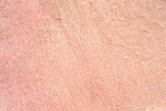 Arena rosada en la playa Foto de archivo