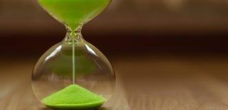 Arena verde en un reloj de arena en un fondo borroso, primer foto de archivo
